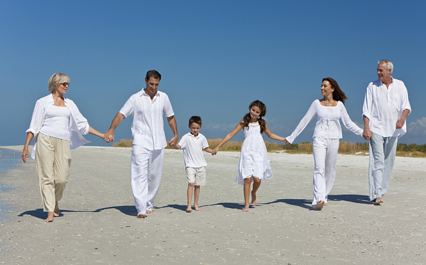 Multi Generational family on beach all in white